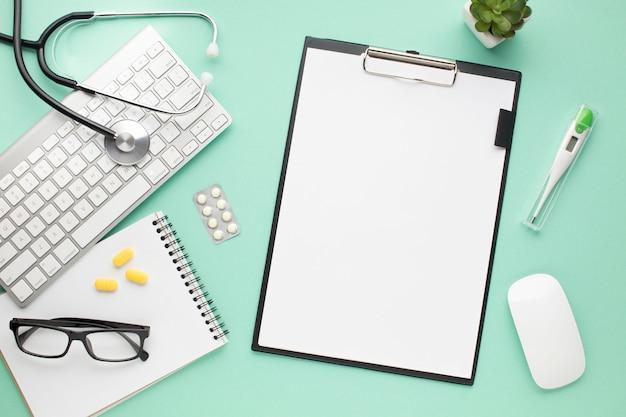 Gezondheidszorgtoebehoren met klembord en moderne apparaten over groene achtergrond