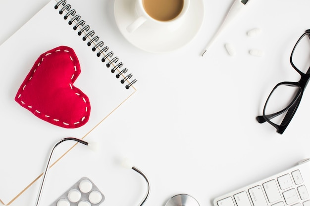 Gezondheidszorgtoebehoren met rood stuk speelgoed hart en spiraalvormige blocnote op witte achtergrond