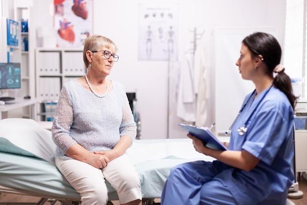 Gezondheidszorgverpleegkundige vertelt senior vrouw diagnose over ziekte