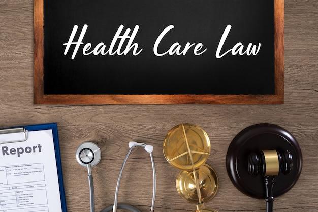 Gezondheidszorgwet inscriptie op bord, rapport, stethoscoop, weegschaal en hamer
