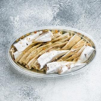 Gezouten ansjovisfilets, in plastic bakje, op grijs