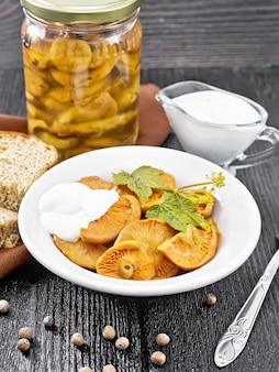 Gezouten champignons saffraan met zure room, krentenblad en takje dille in plaat, vork, servet en brood op de achtergrond van houten plank