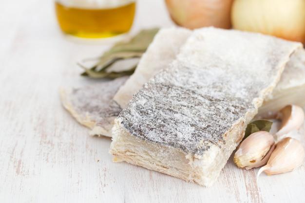 Gezouten droge kabeljauw met olie, knoflook en ui op houten oppervlak