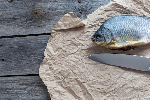 Gezouten droge visvobla met een scherp mes op verfrommeld kraftpapier op houten