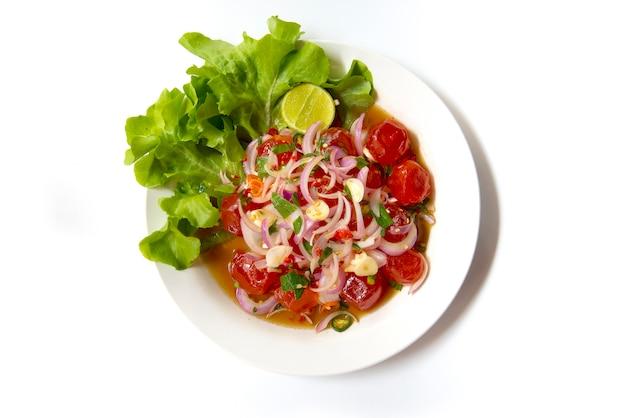 Gezouten eigeel spicy salad chili paste. thais voedsel op schotel die op witte achtergrond wordt geïsoleerd