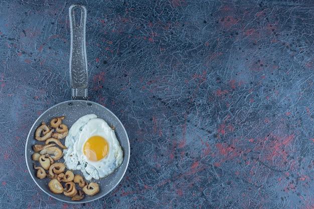 Gezouten en gekruid gebakken ei met peterselie op een koekenpan.