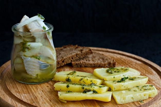 Gezouten haring in een pot met gekookte aardappelen en groene saus.