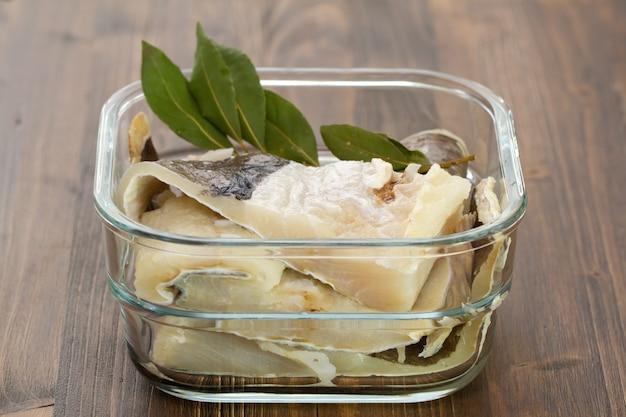 Gezouten kabeljauwvissen in water in glasschotel op bruin