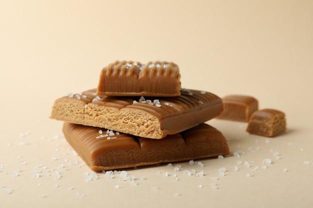 Gezouten karamel stukken op beige achtergrond, close-up