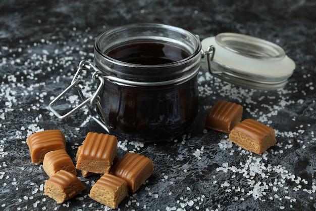 Gezouten karamelstukjes en saus op zwarte rokerige achtergrond