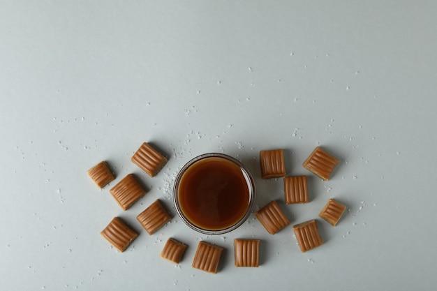 Gezouten karamelstukken en kom met saus op lichtgrijze achtergrond