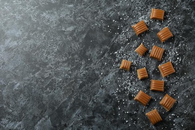 Gezouten karamelstukken op zwarte rokerige achtergrond, ruimte voor tekst