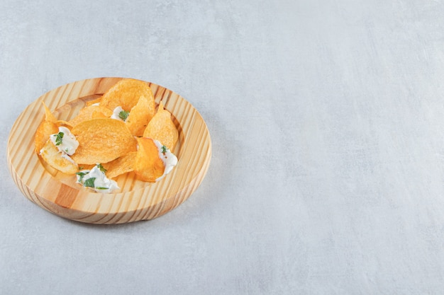 Gezouten knapperige chips en verse yoghurt op houten plaat.