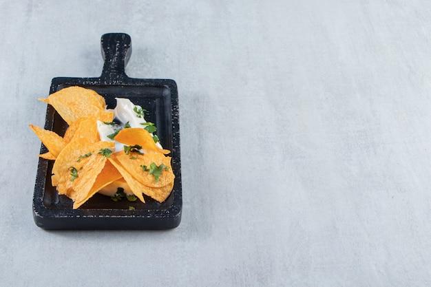Gezouten knapperige chips en verse yoghurt op zwarte snijplank.