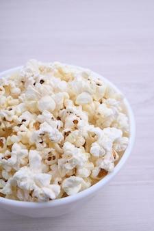 Gezouten popcorn in een kom op een houten tafel. bovenaanzicht.
