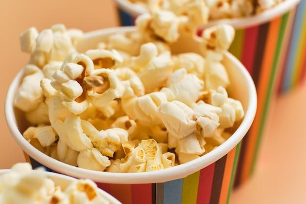 Gezouten popcorn in papieren bekers op een beige ondergrond