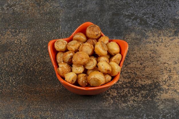 Gezouten smakelijke crackers in een stervormige kom.