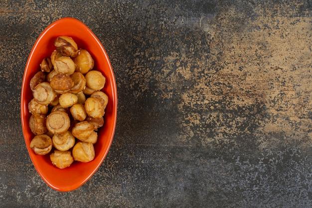 Gezouten smakelijke crackers in oranje kom.