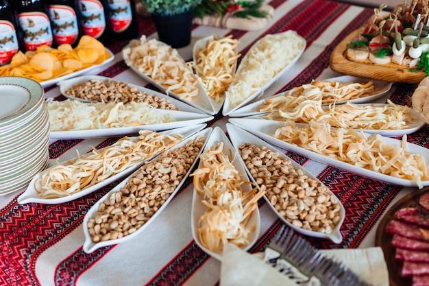 Gezouten snacks liggen in lange witte gerechten