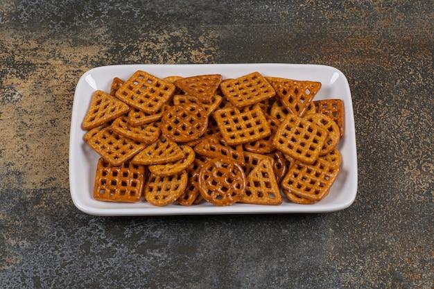 Gezouten verschillende crackers op witte plaat.