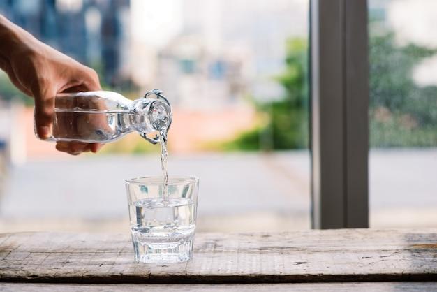 Gezuiverd vers drinkwater uit de fles op tafel in de woonkamer gieten