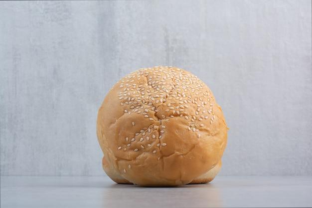 Gezwollen broodje met sesamzaadjes op stenen oppervlak