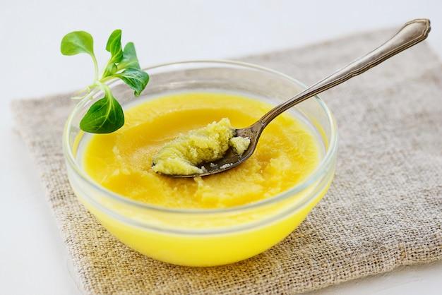 Ghee boter met greens in een kom op een grijs servet.