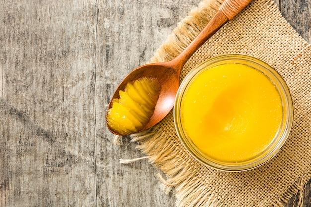 Ghee of geklaarde boter in pot en houten lepel op houten tafel