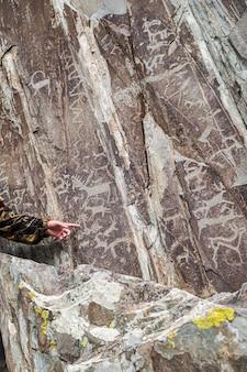 Gidshand die naar rotstekeningen op een rots wijst foto genomen bij adyrkan-schrijn in het altai-gebergte