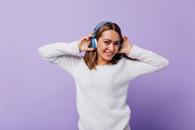 Giechelende jonge vrouw in goed humeur schattig haar koptelefoon aan te raken. meisje met kort donker haar poseert gelukkig op lila