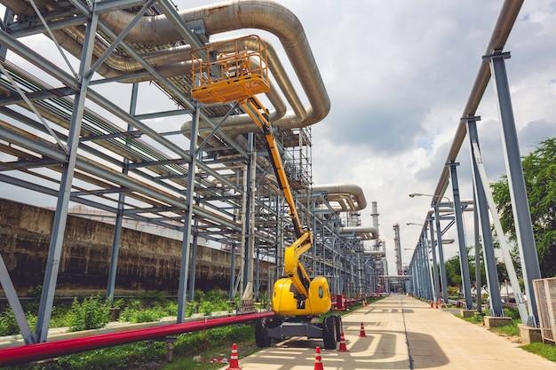 Gieklift werkt op hoogte bij een inspectie van de olie-industrie voor pijpleidingen
