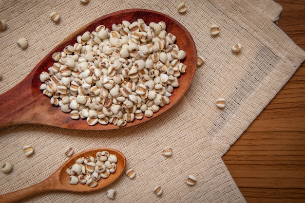 Gierst in een houten lepel die granen en voedsel op een bruin tafelkleed is
