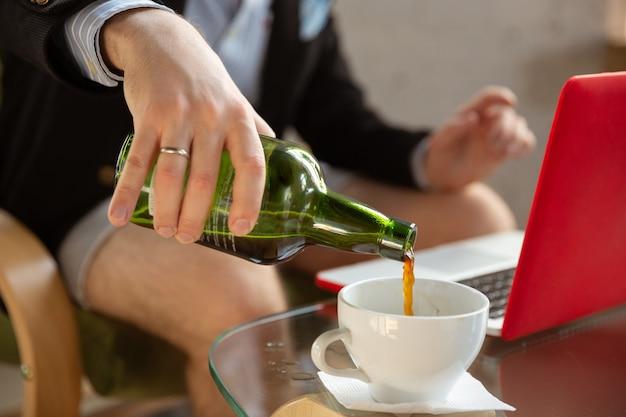 Giet alcohol jonge man zonder broek maar in jas aan het werk op een computerlaptop