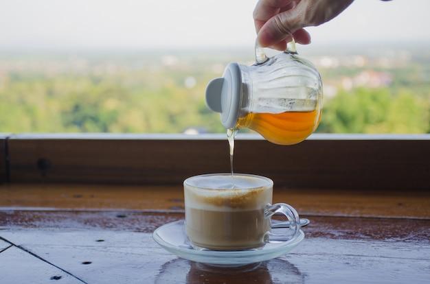 Giet de honing in het koffiekopje.