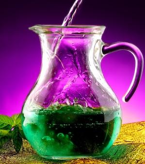 Giet groene vloeistof op een glazen pot