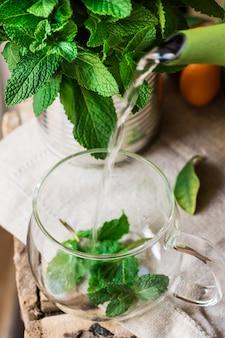 Giet heet opspattend water uit de pot in een glazen beker met verse kruidenthee