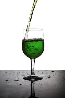 Giet het groene water in een glas wijn.
