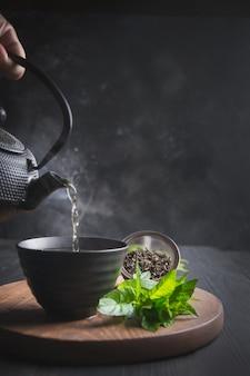 Giet hete thee met stoom in een kopje op zwarte tafel.