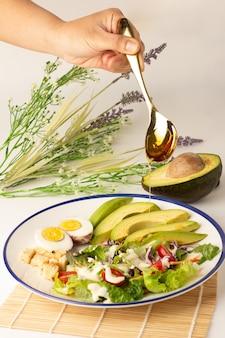 Giet honing van lepel tot salade bestaande uit gesneden avocado, gekookt ei, sla, sla, tomaat en koekjes, gegarneerd met slaroom, avocado doormidden gesneden op de rug, een maaltijd met veel groenten.