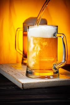 Giet licht bier in mokken