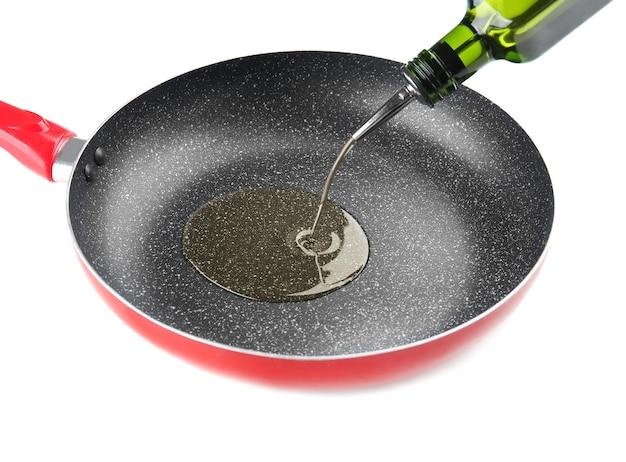 Giet olie in de koekenpan op een witte ondergrond
