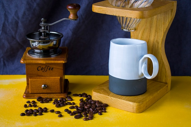 Giet over koffiezetapparaat, koffiekopje en mok, studio-opname