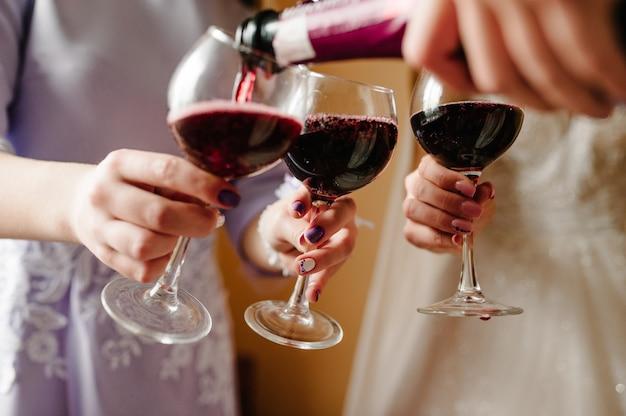 Giet rode wijn. bruid en bruidsmeisjes roosteren met champagne en plezier op huwelijksochtend.