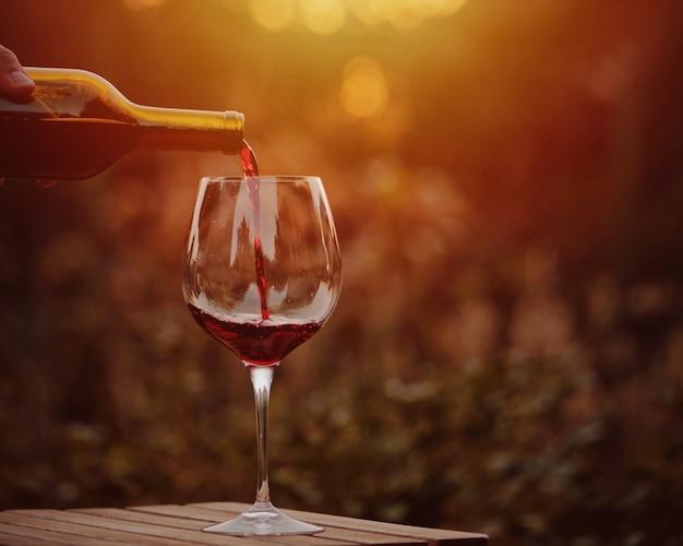 Giet rode wijn. wijnglas rode wijn in het dorp bij zonsondergang.