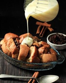 Giet vanille vla aan de vers gebakken broodpudding gemaakt van gesneden stokbrood met rozijnen en kaneel, op zwarte houten tafel