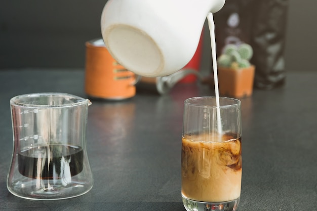 Giet verse melk in een zwarte koffiekop.