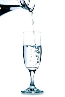 Giet water in het glas uit de kan