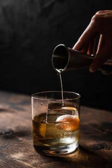 Giet whisky van een jigger in een rotsglas met een groot ijsblokje, achterlicht