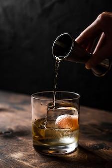 Giet whisky van een jigger in een stenen glas met een groot ijsblokje