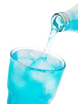 Gieten blauwe soda in glas met ijs uit fles geïsoleerd op een witte achtergrond